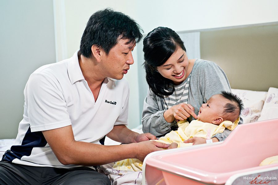 Mother and father with newborn baby in hospital