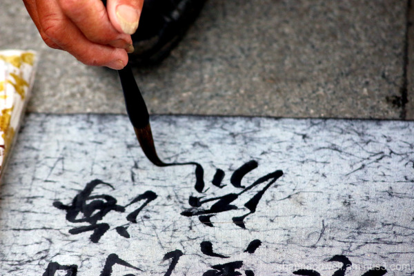 Man writing Chinese calligraphy characters