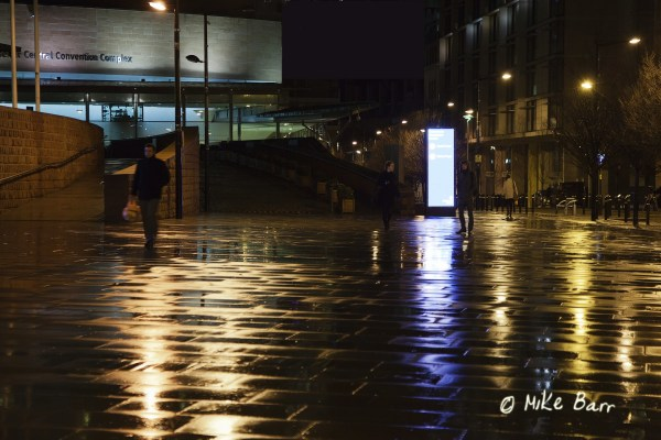 People hurrying on a wet pavement in Manchester