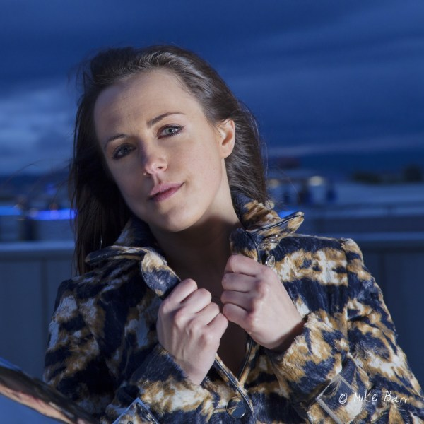 portrait of young woman model against evening sky