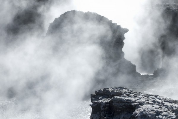 Hot steam over volcanic rocks