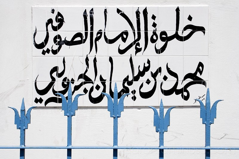 Arabic sign over blue fence