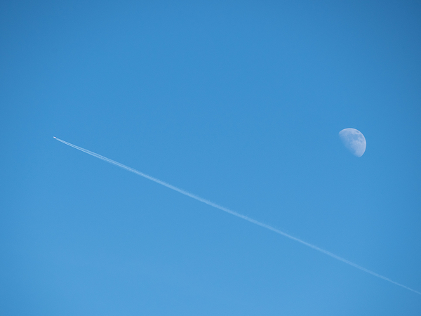 plane passing three-quarter moon