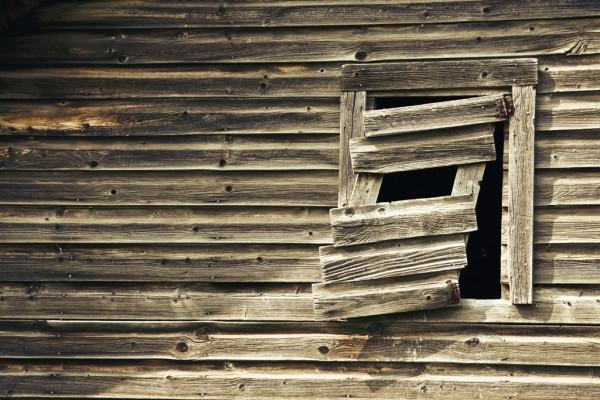 Abandoned farmhouse window slightly askew