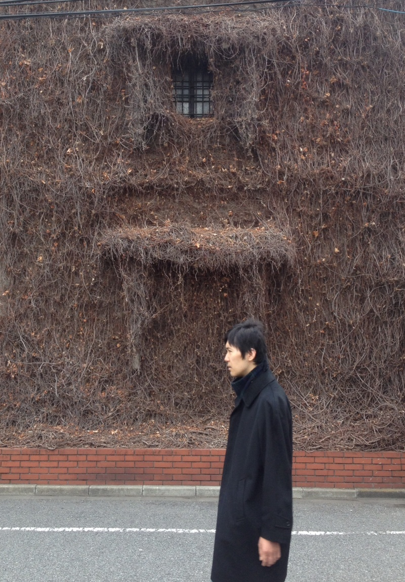 Man waking past a vine-covered building