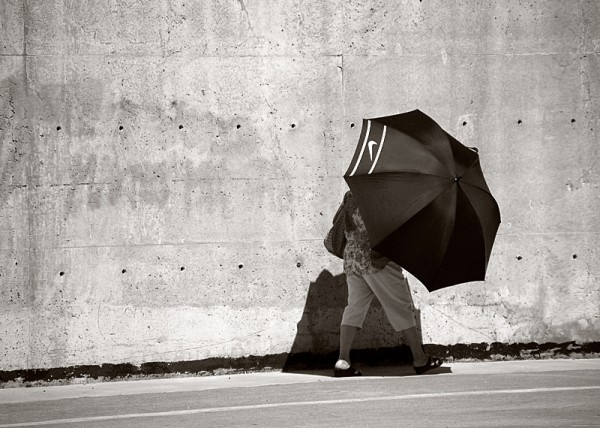 Lady shielding herself from sun with umbrella.