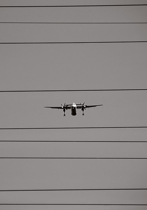 Plane flying between tension lines.