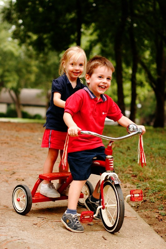 2 kids play on a Radio Flyer tricycle