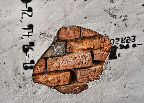 Bricks comming through a plaster Wall