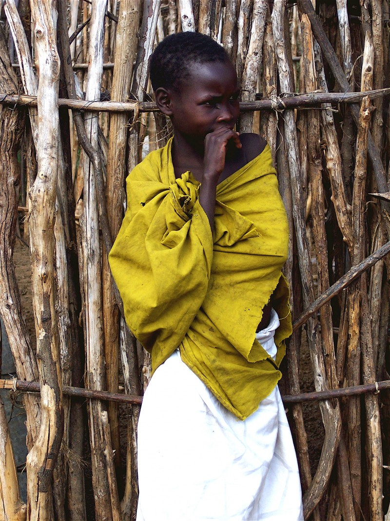 A Kenyan boy resting against the wall of his home.
