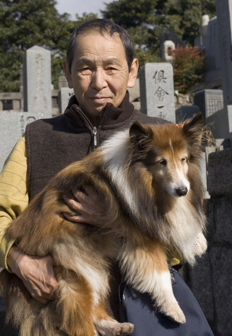 A man carrying his dog.