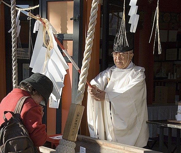 A Shinto priest blesses a lady.