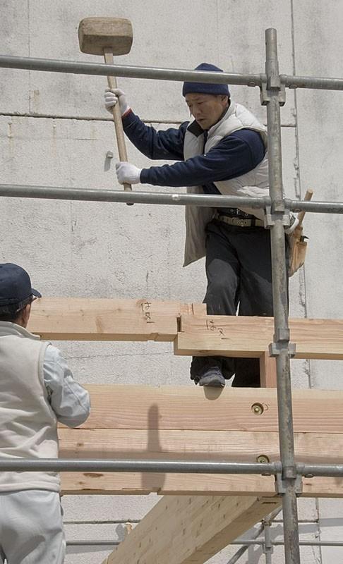 A man assembling a building.