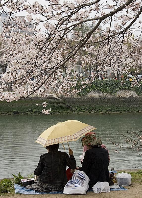 Some women sharing an umbrella.