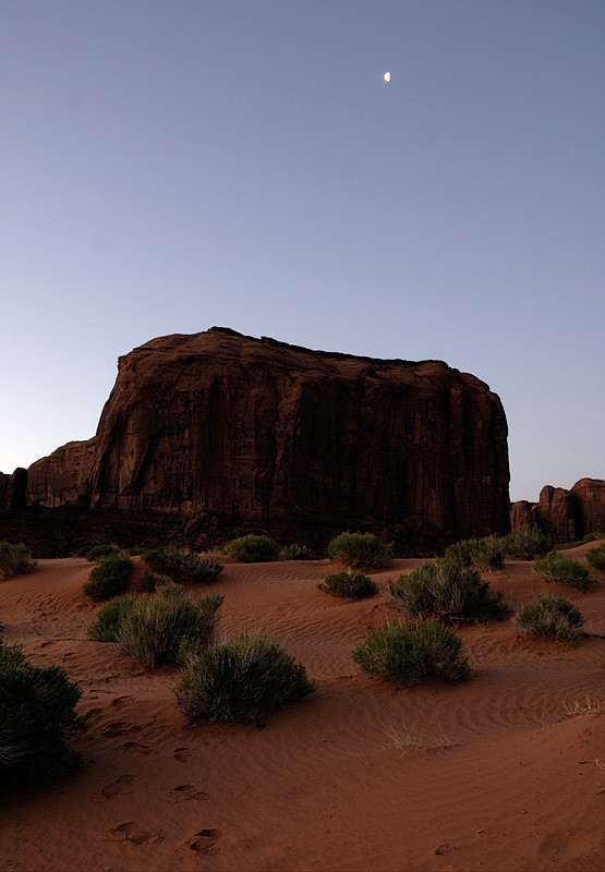 The moon over a big rock in Monument Valley.