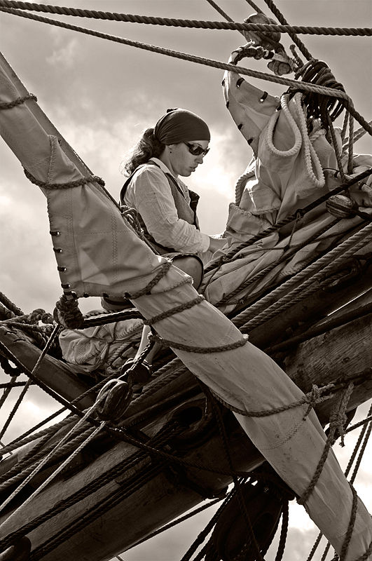 A lady readies sails on a ship.