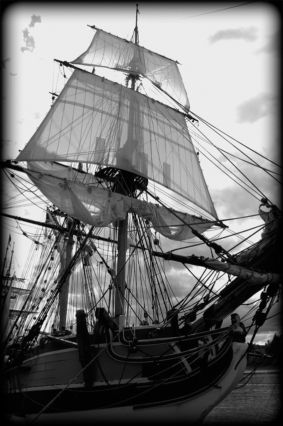 A ship with its sails being set.