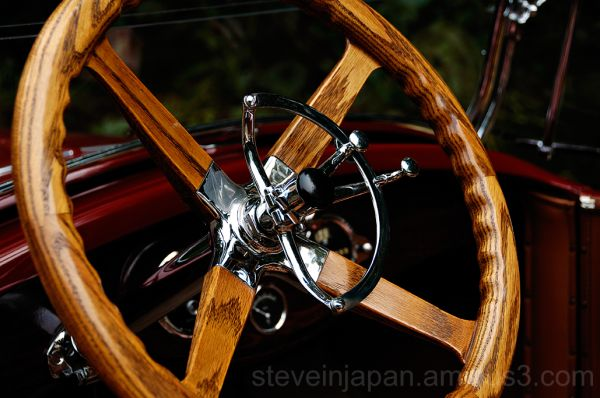 An oak steering wheel in an antique car.