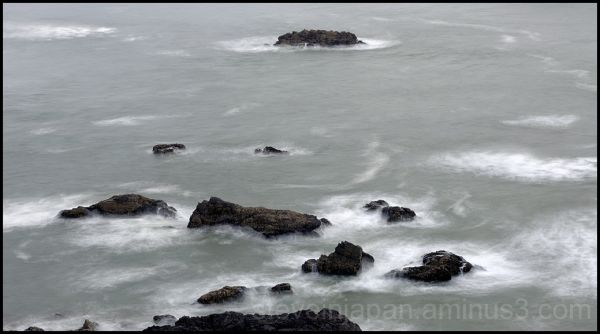 Rocks in the swirling surf.