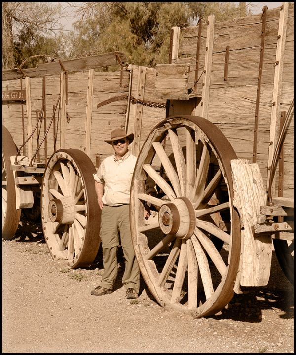 A man by a 20 mule team wagon in Death Valley.