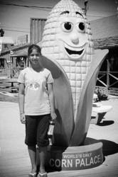 A girl standing beside a big ear of corn.