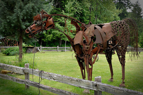 A rusty horse made of scrap metal and horse shoes.