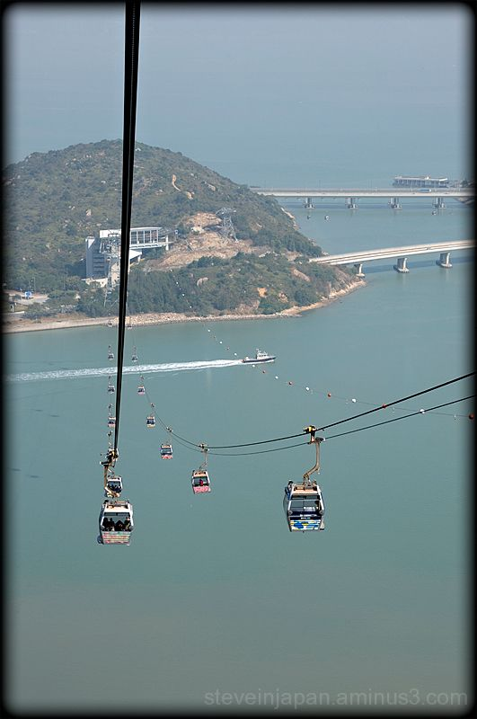 The cars of the Ngong Ping 360 rise high.