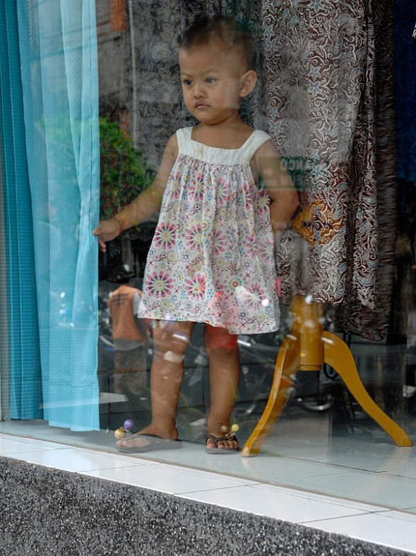 A girl in a shop window along Monkey Forest Road.