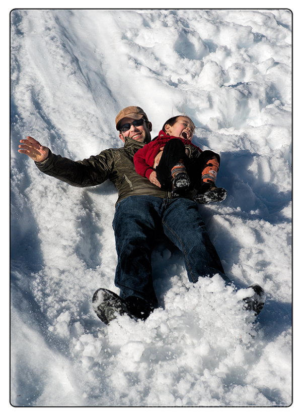 Alex and his dad sliding on the snow.