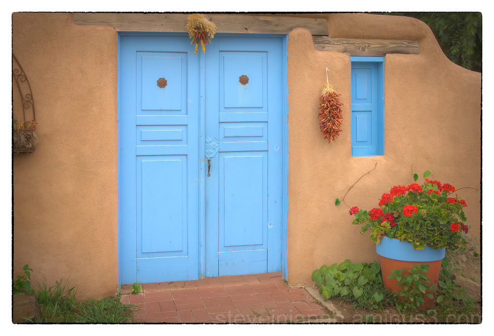A wall & blue doors in Taos, New Mexico.