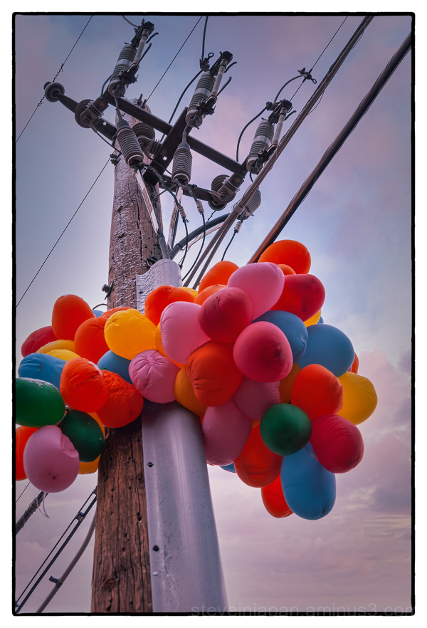 Balloons caught on a power pole.