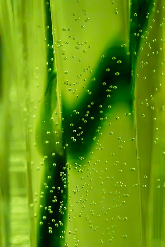 Green abstract of a vase with a rose stem in it.