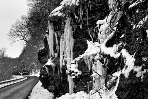 Icicles hanging from cliff next to roadway