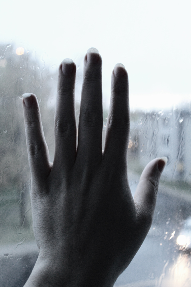 hand against a rainy window