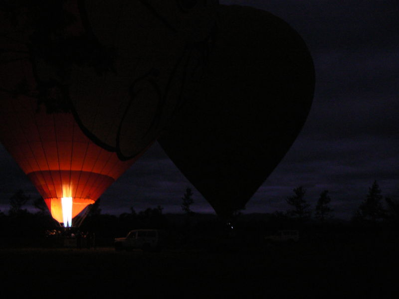 Hot air balloons standing in the dark before dawn