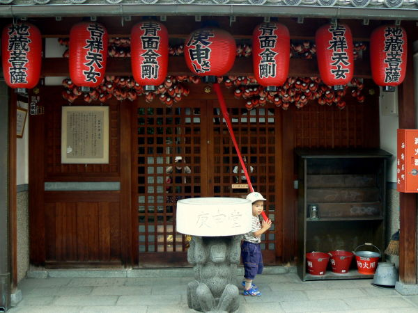 Small boy rings bell at roadside shrine in Nara