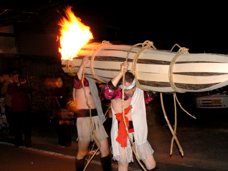 Men carrying a huge burning torch