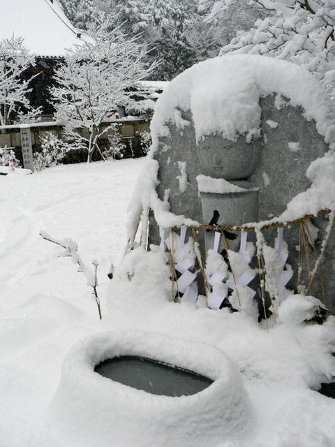 Japanese statue and water basin in snow