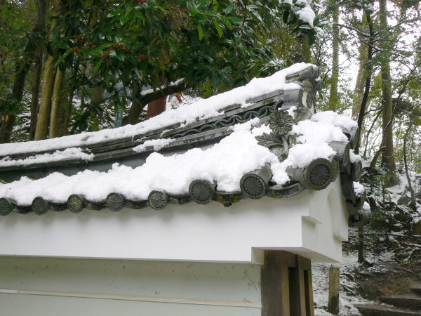 Snow piling on a wall in a Japanese temple garden