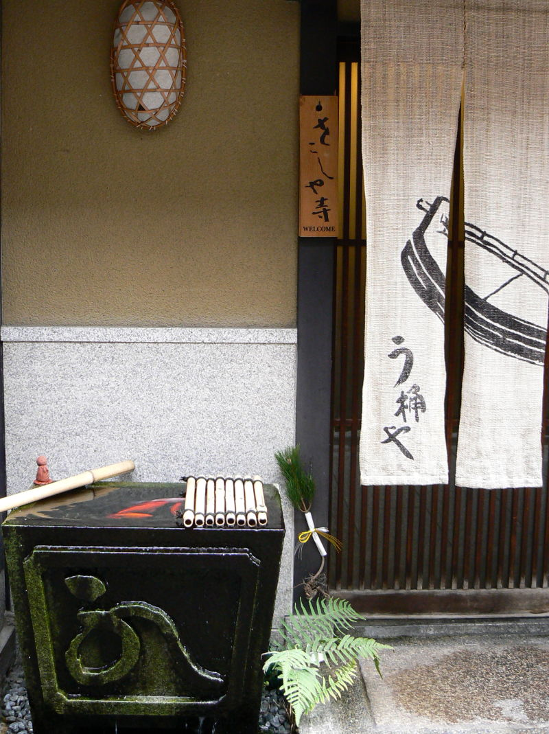 Stone koi pond beside a Japanese doorway
