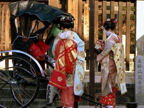 Two Japanese Maiko standing beside rickshaw