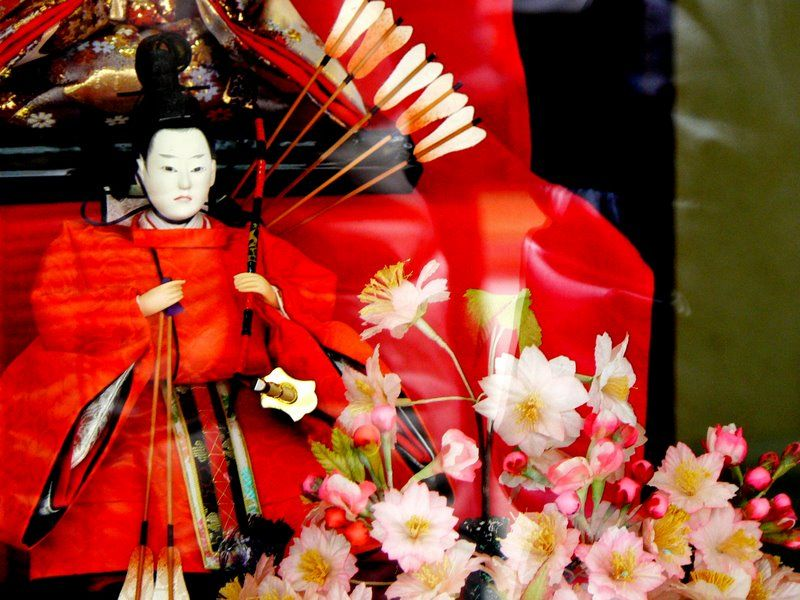 Japanese archer doll with flowers in foreground