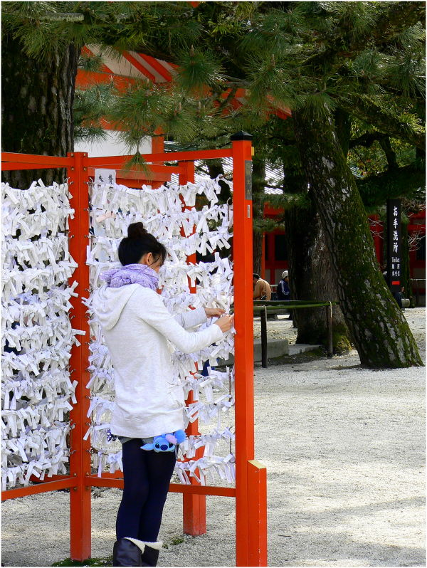 Japanese girl ties slip of paper to stand