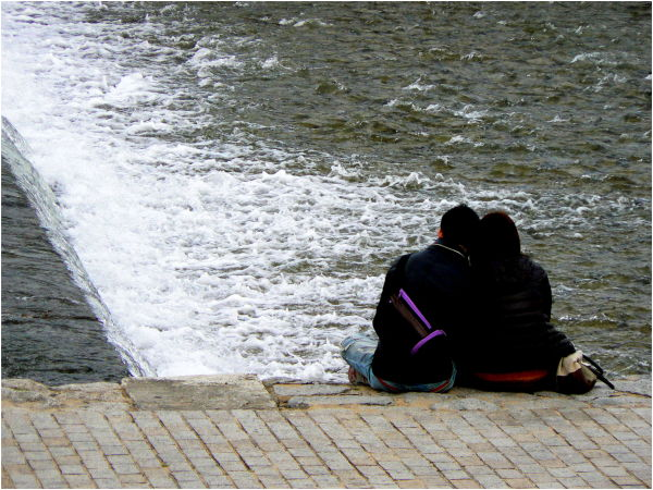 Couple sitting beside Kamo River
