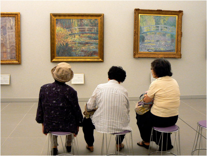 three women sitting in an art museum