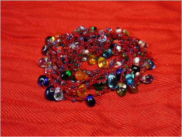 Necklace of glass beads on a red background