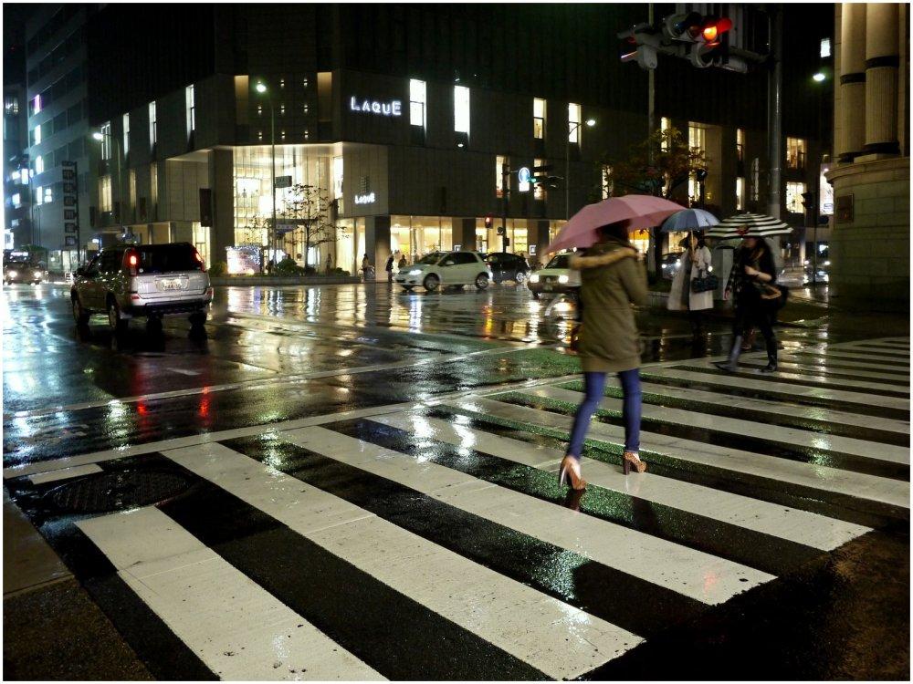 Woman with umbrella crossing street on rainy night