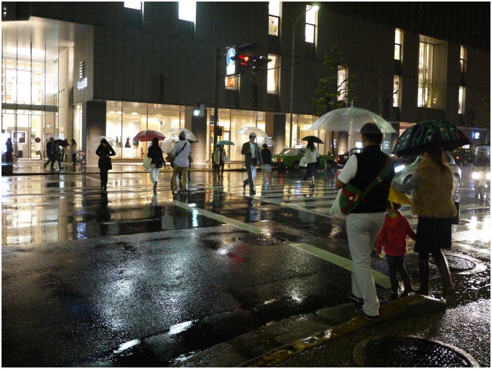 People crossing city street on rainy night