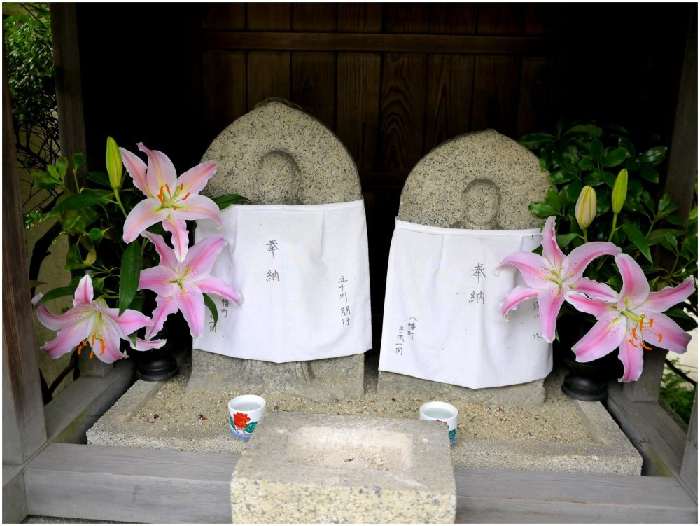 Japanese O-jizo shrine with pink lilies