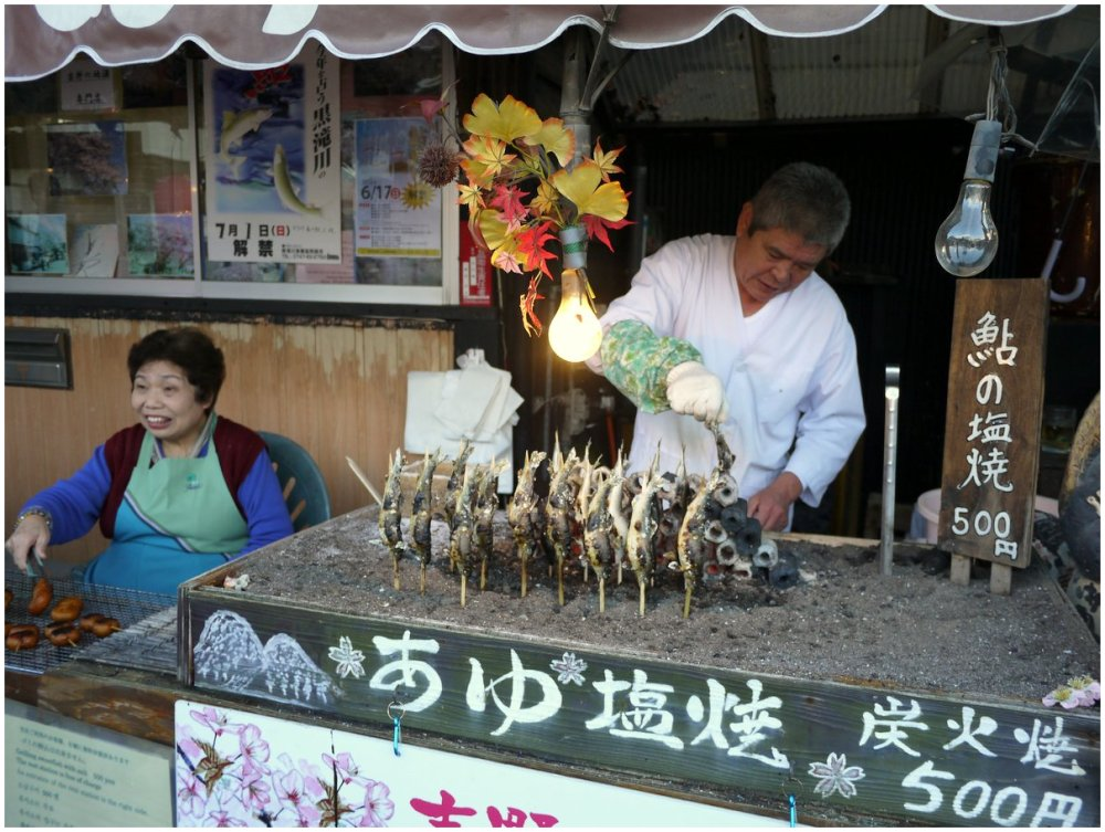 Couple selling grilled fish from a roadside stall